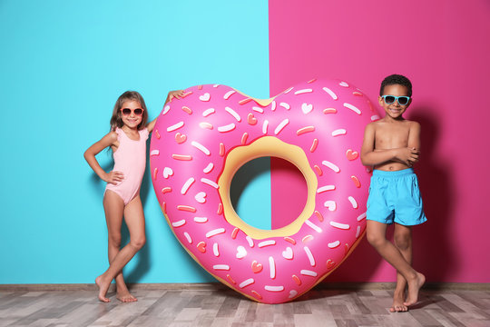Cute little children with bright heart shaped inflatable ring near color wall