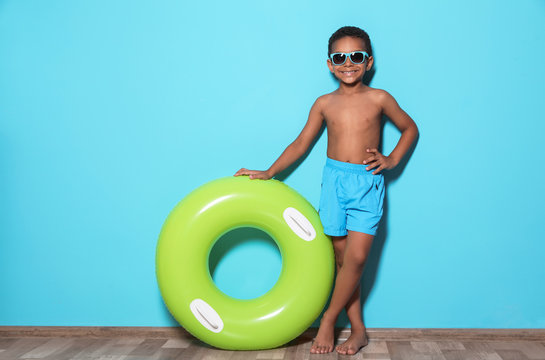 Cute African American boy with bright inflatable ring near color wall