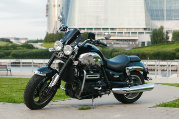 Middle shot of a black motorcycle in front of a city river.