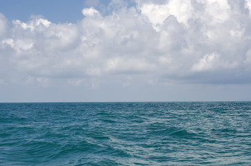 Smooth sea surface against a background of a cloudy sky.