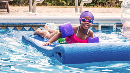 A young African girl is enjoying swimming at summer time