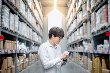 Young Asian man checking the shopping list looking for product in warehouse wholesale, shopping warehousing concept