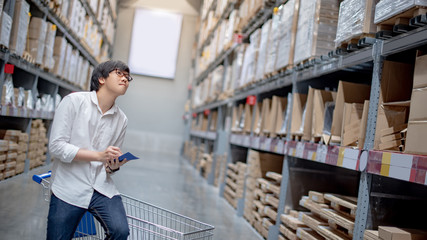 Young Asian man standing with cart checking the shopping list and looking for product in warehouse wholesale, shopping warehousing concept