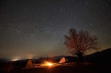 Fantastic night camping site view. Bright bonfire burning between two tourist tents under beautiful dark starry sky on big tree and distant mountain range background. Tourism, outdoor activity concept