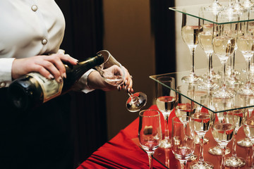 Elegant waiter pouring sparkly champagne into group of glasses at luxury business corporate retreat party, restaurant catering concept