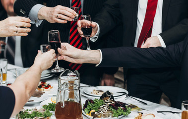 Corporate business man toasting at dinner party table hands close-up, wedding reception guests toast alcohol drinks in glasses for newlyweds, happy people drinking, celebration concept