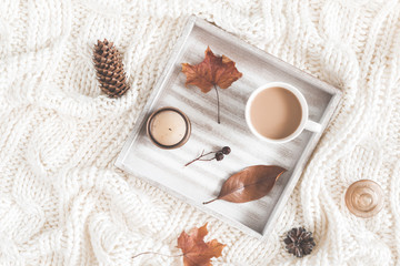 Autumn composition. Cup of coffee, blanket, dried autumn leaves on white background. Flat lay, top view