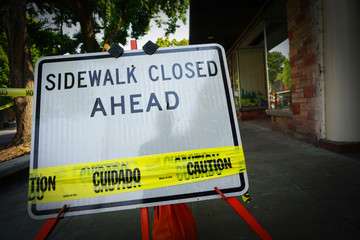 sidewalk closed sign with caution tape