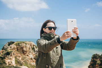 A young tourist girl takes pictures on a tablet or shoots a video for memory or talks to someone online with the help of messengers or via the Internet. Atlantic Ocean in the background.