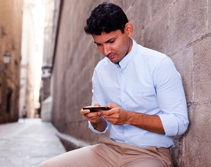 modern guy walks in city and communicates on smartphone