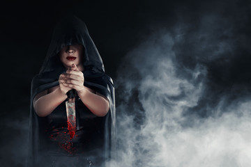 Witch woman holding a bloody knife with smoky background