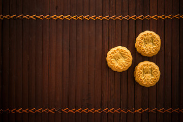 Moon cakes on bamboo mat low light with copy space
