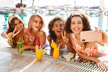 Four happy young women in swimwear