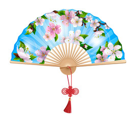 Chinese fan with a pattern of pink spring sakura flowers on blue sky. On the handle of the folding fan red wishful knot. Isolated on white background.