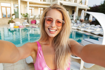 Happy young woman in swimsuit, sunglasses