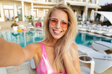 Smiling young woman in swimsuit, sunglasses