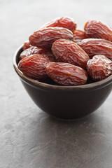 Fresh Medjool Dates in a bowl. Ramadan kareem. Black background. Copy space.