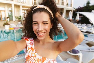 Smiling young woman in swimsuit taking a selfie