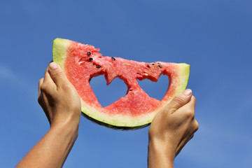 double follower of summer/ slice of watermelon with hearts in raised hands against the sky
