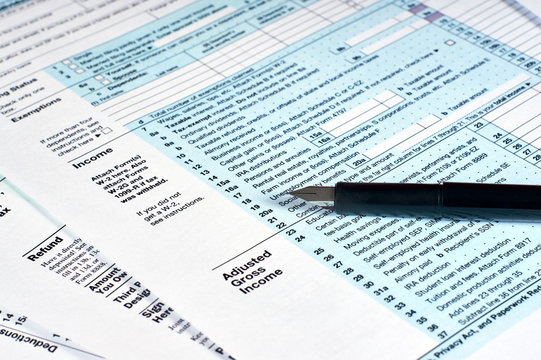 Tax reporting and pen. Filling out tax forms