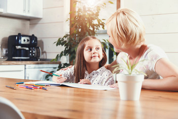 Beautiful blond mother and cute brunette little daughter drawing with color pencils on the light kitchen, family concept