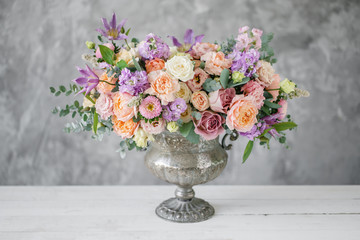 Obraz Gorgeous bouquet of different flowers. floral arrangement in vintage metal vase. table setting. lilac and peach color - fototapety do salonu