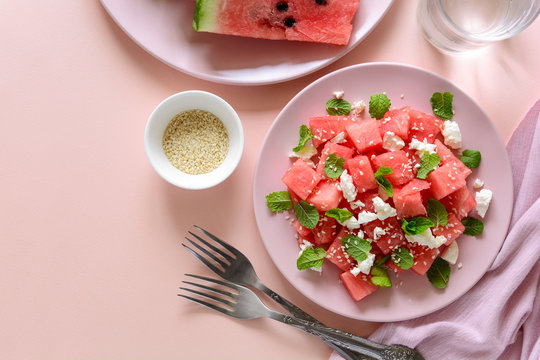Summer watermelon salad with feta cheese, sesame seeds and mint leaves on pink plate. Healthy eating concept