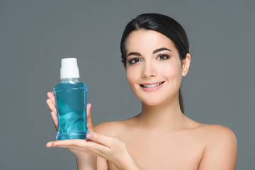portrait of smiling woman with bare shoulders holding mouthwash isolated on grey