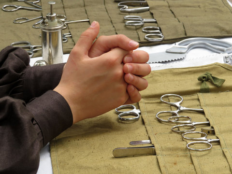 Female hands on the background of old surgical instruments. Concept for military field hospital, a historical reconstruction of medicine in 19th century