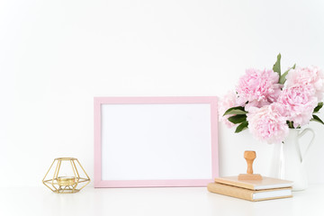 Pink landscape frame mock up with a pink peonies, candle and stamp beside the frame, overlay your quote, promotion, headline, or design, great for small businesses, lifestyle bloggers