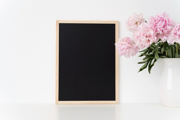 White portrait frame mock up with a pink peonies beside the frame, overlay your quote, promotion, headline, or design, great for small businesses, lifestyle bloggers and social media