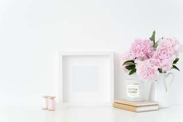 White square blank frame mockup. Still life composition, floral elegant bouquet of pink peonies in jug, silk ribbons. Background, mock up for quote, promotion, headline and social media