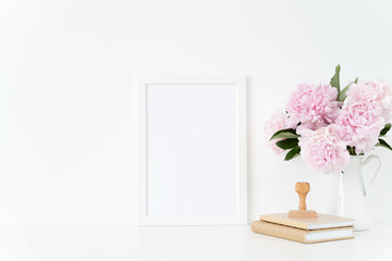 White blank frame mockup. Still life composition, floral bouquet of pink peonies in jug, stamp. White background, mock up for quote, promotion, design, lifestyle bloggers and social media