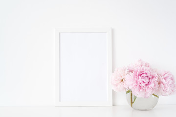 Minimal feminine white blank a4 frame mockup. Floral bouquet of pink peonies in transparent vase. Background, mock up for quote, promotion, headline, design, lifestyle bloggers and social media
