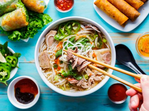 eating colorful vietnamese pho bo with chopsticks from top down view