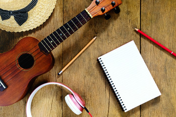 Top view wooden table, There are notebooks, pencils, hats, earphones, and ukulele on the wood table, relaxation shots. Music concept
