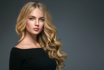Foto auf Acrylglas Friseur Blonde hairstyle woman beauty with long curly blonde hair over dark background