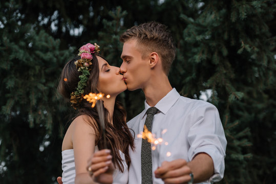 beautiful happy young wedding couple kissing and holding sparklers