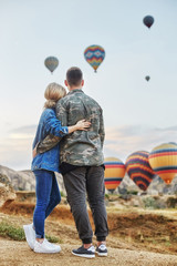 Couple in love stands on background of balloons in Cappadocia. Man and woman on hill look at a large number of flying balloons. Turkey Cappadocia fairytale scenery of mountains. Wedding on nature