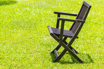 Black wooden chairs on the lawn.