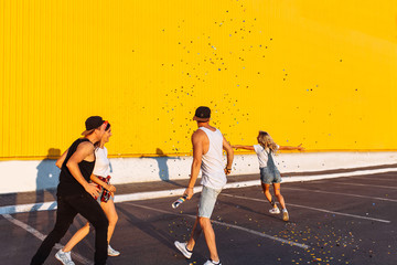 Beautiful cool young jump with confetti on a yellow background, a group of young people celebrating and having fun, summer mood, friends walking in the city in place, lifestyle