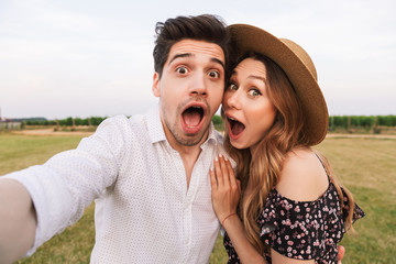Joyful beautiful couple man and woman dating, and taking selfie together while walking outdoor through field