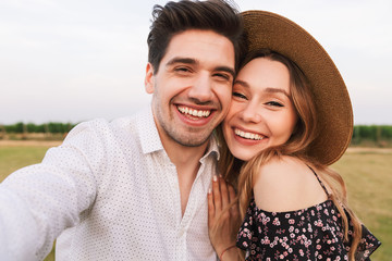 Lovely smiling couple man and woman dating, and taking selfie together, while walking outdoor through field