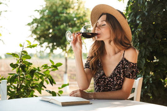 Photo of caucasian pretty woman wearing straw hat drinking wine, while sitting at table and reading book outdoor in countryside