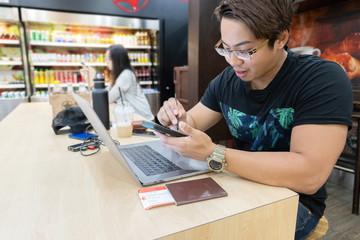 Traveler man using internet on smart phone and laptop, waiting for airplane flight