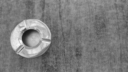 Steel metal empty ashtray on a gray table. View from above
