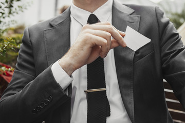 Close up of businessman putting blank business card in his jacket pocket.