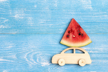 Wooden toy car with slice of watermelon on the roof on blue background. Copy space for text, top view.