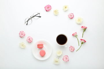Rose flowers with cup of coffee and macarons on white background
