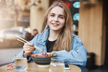 Lifestyle blogger making review on new asian restaurant in city centre, leaning on table while standing outside, holding chopsticks near bowl with soba, gazing with satisifed expression at camera
